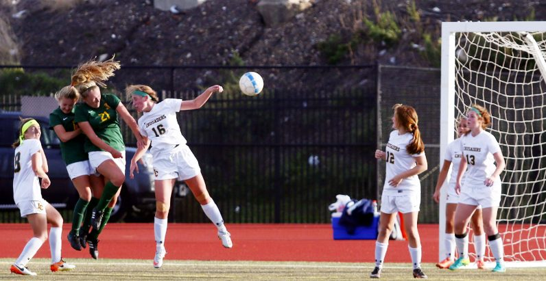 Sophia Filippo (no. 21, green) heads the ball into the Lansdale Catholic net for the winning goal in overtime as Archbishop Wood won the Oct. 29 game, 2-1, and captured the Catholic League championship. (Sarah Webb)
