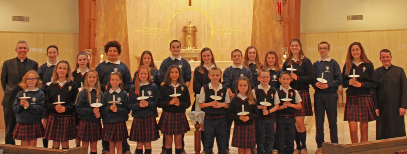 The officers and representatives of Holy Cross Regional School's Student Council for the 2016-2017 school year show the candles they lit to signify the Christ-like spirit of the Catholic school in Collegeville, Montgomery County. Also shown at far left is the pastor of St. Eleanor Parish, Msgr. Michael McCulken, and at far right, Father Christopher Moriconi, parochial vicar.