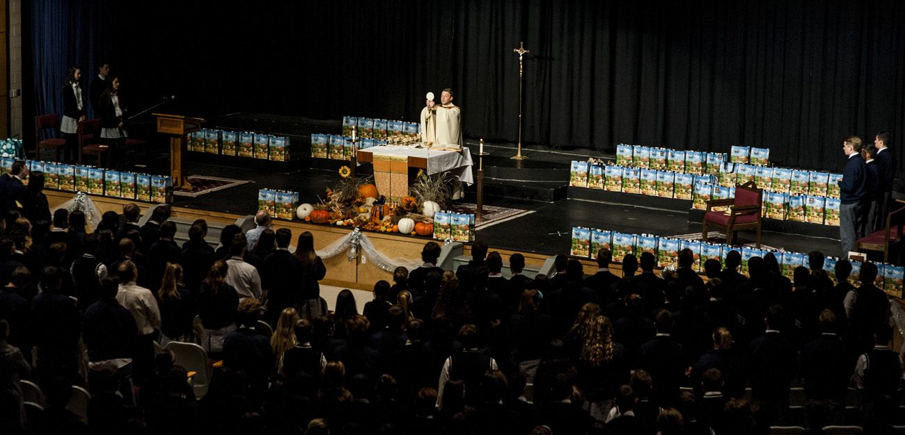 Father Brian Kean celebrates Mass for Pope John Paul II High School students Nov. 22, as the 130 Thanksgiving meal bags the students collected line the stage.