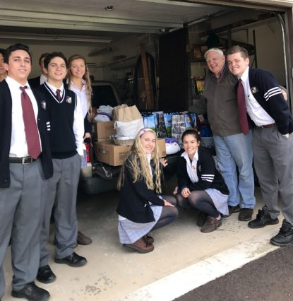 Students of Pope John Paul II High School load into a truck some of the meals collected for the needy.