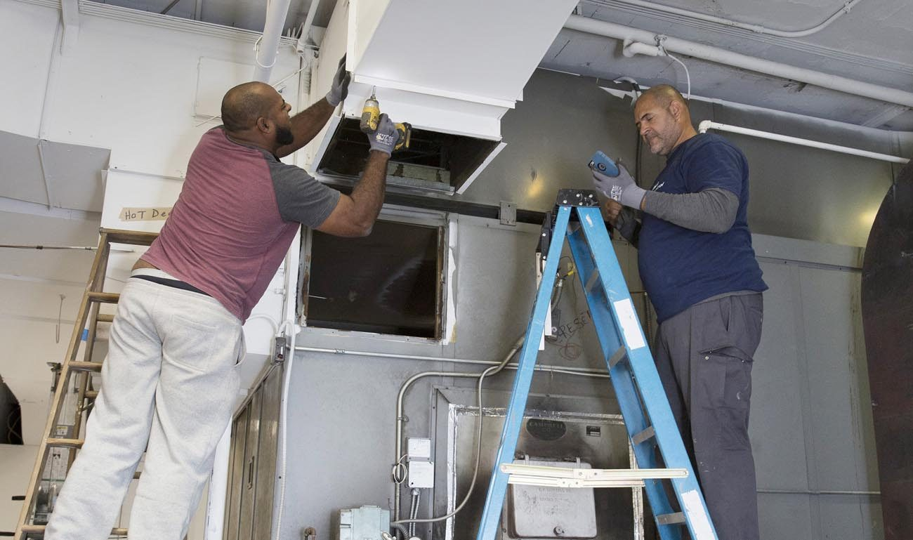 Workers remove an old heating and cooling system at Our Lady of Sorrows Church in Takoma Park, Md., Nov. 1. A parish debt relief program instituted by the Archdiocese of Washington to coincide with the Year of Mercy has enabled some parishes to move forward on pastoral programs and needed repairs and renovations. (CNS photo/Jaclyn Lippelmann, Catholic Standard)