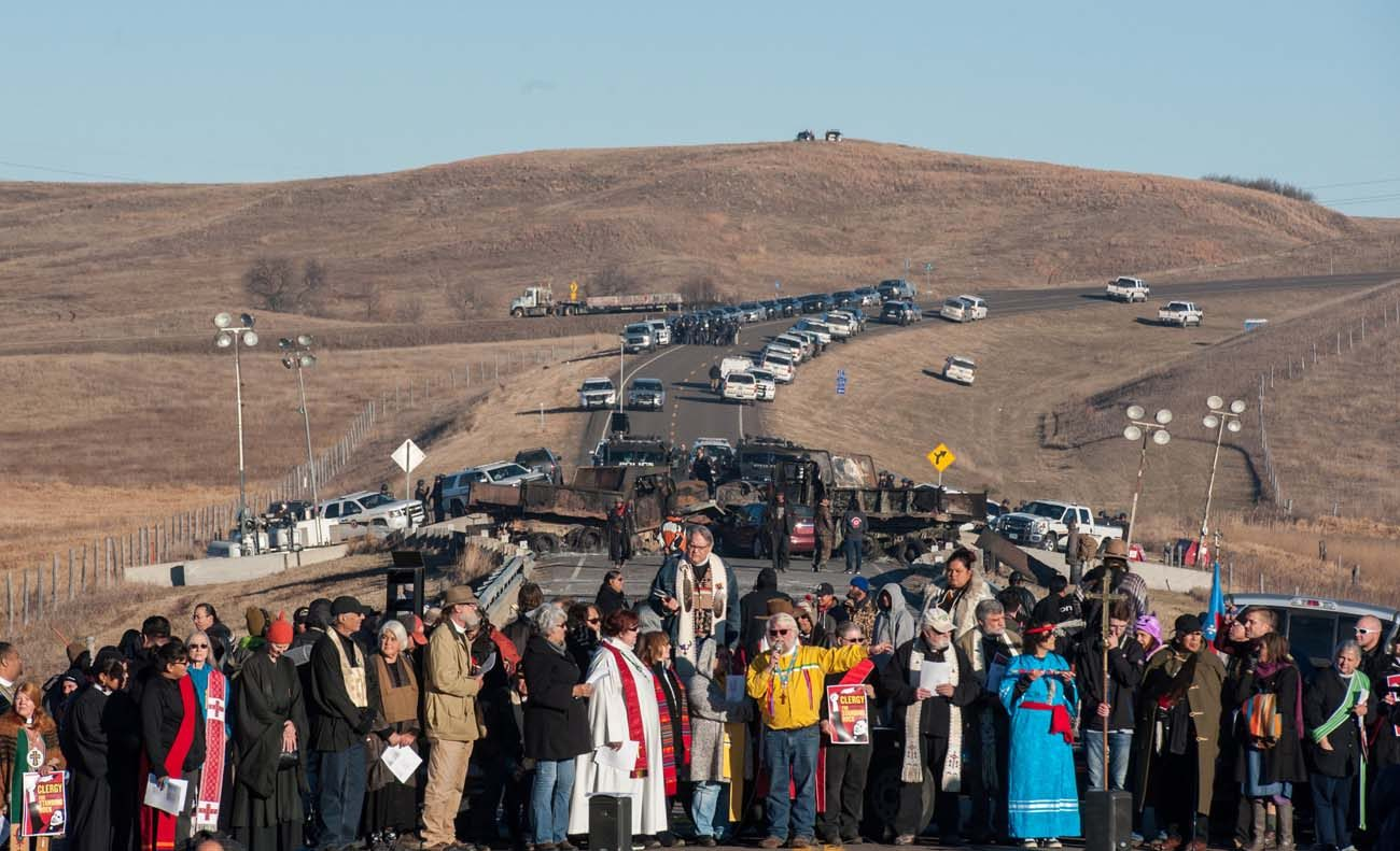 Clergy of many faiths from across the United States participate in a prayer circle Nov. 3  in front of a bridge in Standing Rock, N.D., where demonstrators confront police during a protest of the Dakota Access pipeline. Demonstrations against the pipeline are taking place on the Standing Rock Indian Reservation near Cannonball, N.D. (CNS photo/Stephanie Keith, Reuters)