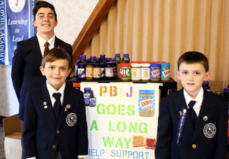 Nick Giangiulio, student body president, Shawn Rinnier, who collected 48 jars, and Jack Gress, who collected 25 jars, represent St. Aloysius Academy, which surpassed its goal of collecting 500 jars of peanut butter and jelly for Nutritional Development Services.