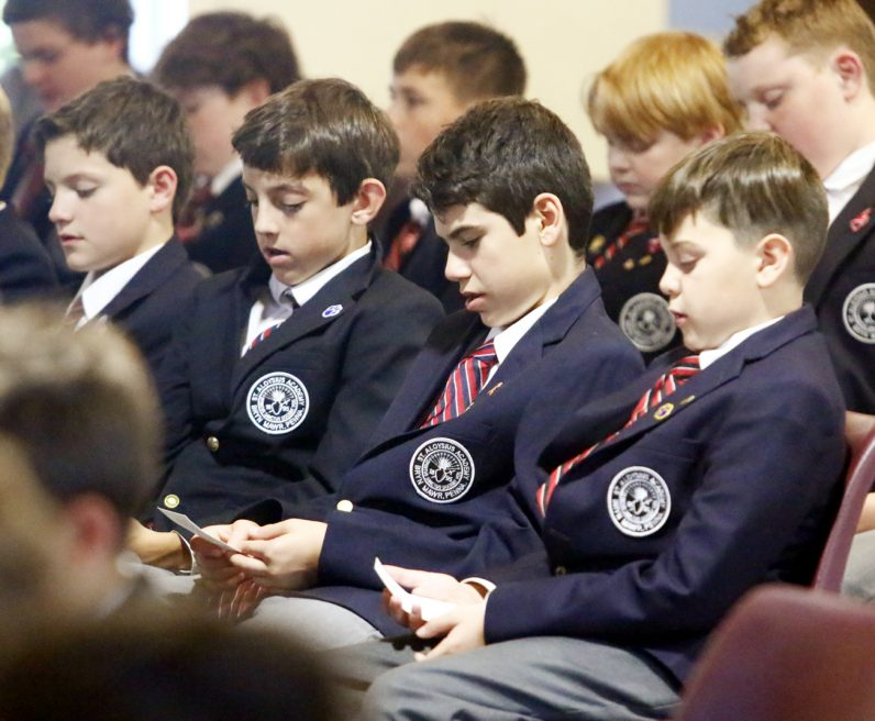 The young men of St. Aloysius Academy pray for those in need.