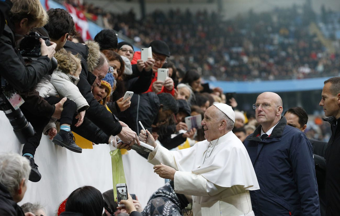 Pope Francis autographs a book before celebrating Mass at the Swedbank Stadium in Malmo, Sweden, Nov. 1. Pope Francis said Nov. 18 that the church is not a prop for one's ego, a soapbox for ideas or a suit of armor protecting a sad life. (CNS photo/Paul Haring)