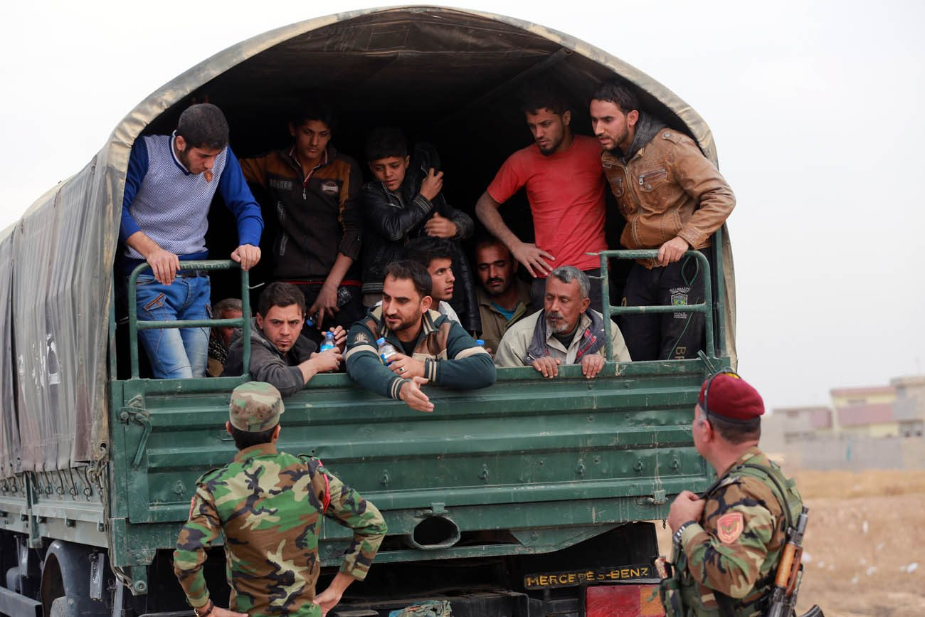 Displaced Iraqis are seen at a checkpoint  in Bartilla, Iraq, Nov. 15. Pope Francis said Nov. 17 that nothing can justify or permit the continued onslaught in the Middle East. (CNS photo/Ahmed Jalil, EPA)