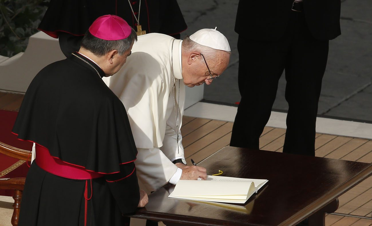 "Pope Francis signs an apostolic letter, ""Misericordia et Misera,"" (Mercy and Misery) after celebrating the closing Mass of the jubilee Year of Mercy in St. Peter's Square at the Vatican Nov. 20. In the letter the pope called for several special initiatives begun during the Year of Mercy to continue on a permanent basis. (CNS photo/Paul Haring)"
