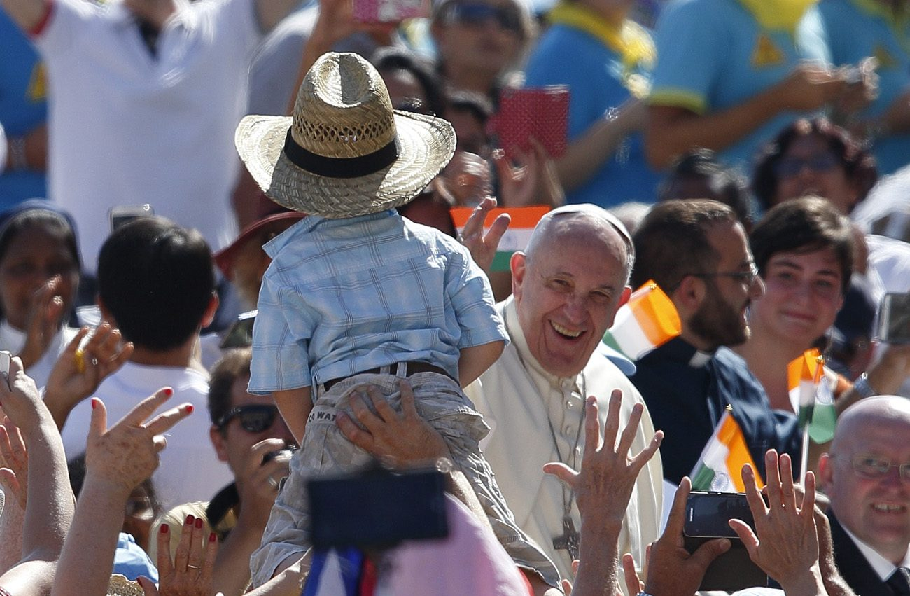"Pope Francis waves to a boy in St. Peter's Square Sept. 3. ""The people of God have a great nose"" for sniffing out priests who serve the god of money more than God the father, Pope Francis told the priests Nov. 18. (CNS photo/Paul Haring)."