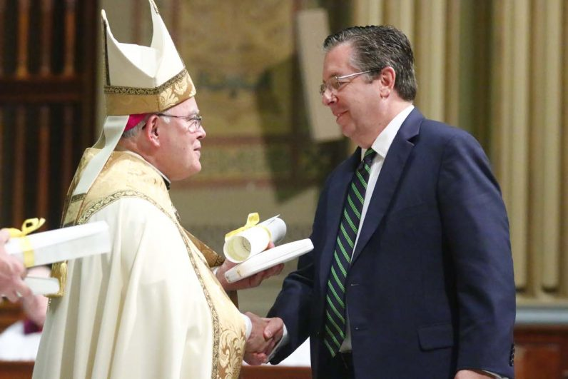 Timothy O'Shaughnessy, chief financial officer for the Archdiocese of Philadelphia who served as special adviser to the World Meeting of Families, receives the Benerementi Medal from Archbishop Chaput.