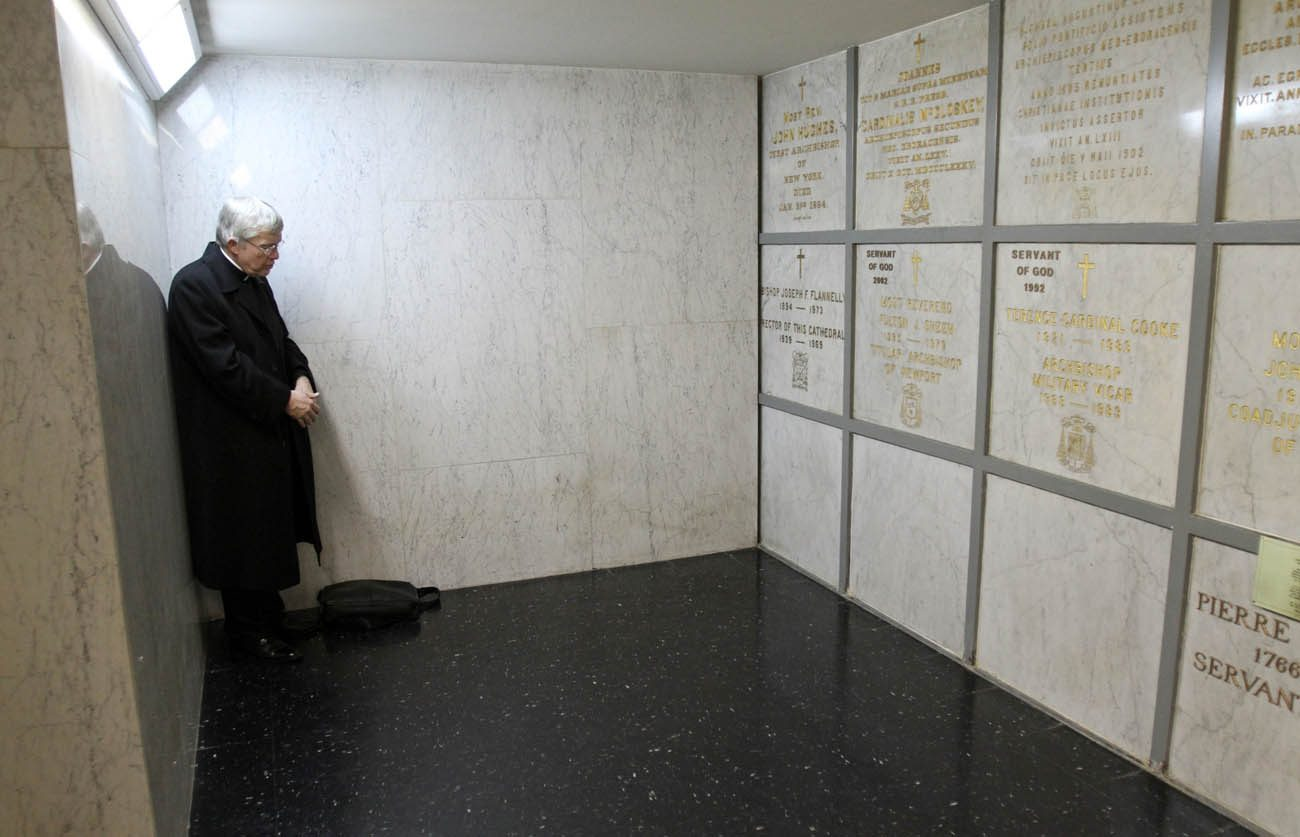 "Father Charles P. Connor prays before the tomb of Archbishop Fulton J. Sheen in the crypt of St. Patrick's Cathedral in New York in this 2009 photo. Father Connor, an assistant professor of church history at Mount St. Mary's University, wrote the book ""The Spiritual Legacy of Archbishop Fulton J. Sheen."" (CNS photo/Gregory A. Shemitz)"