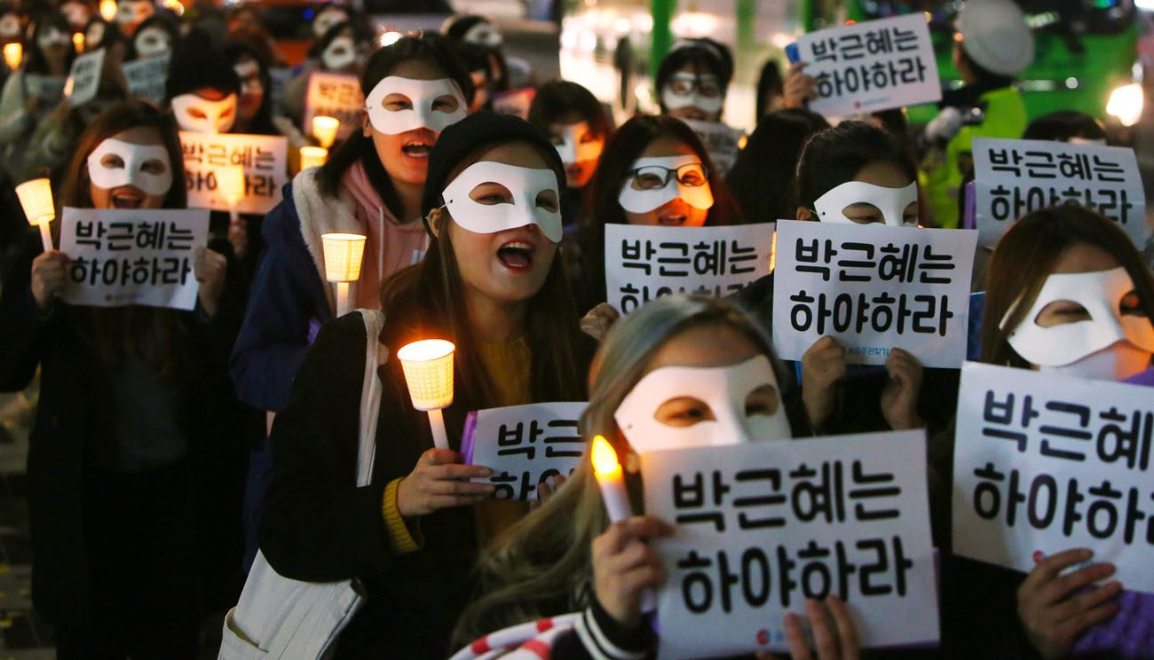 "South Korean university students carry candles and placards that read ""Park Geun-Hye Step Down"" Nov. 15 in Seoul. The South Korean president is embroiled in scandal involving a longtime friend. (CNS photo/Yang Ji-Woong, EPA)"