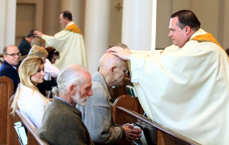 Father Anthony Rossi lays hands on Bill Feathers.