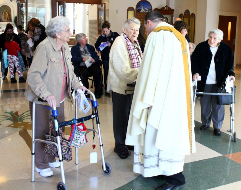 Father Anthony Rossi greets guests after Mass.