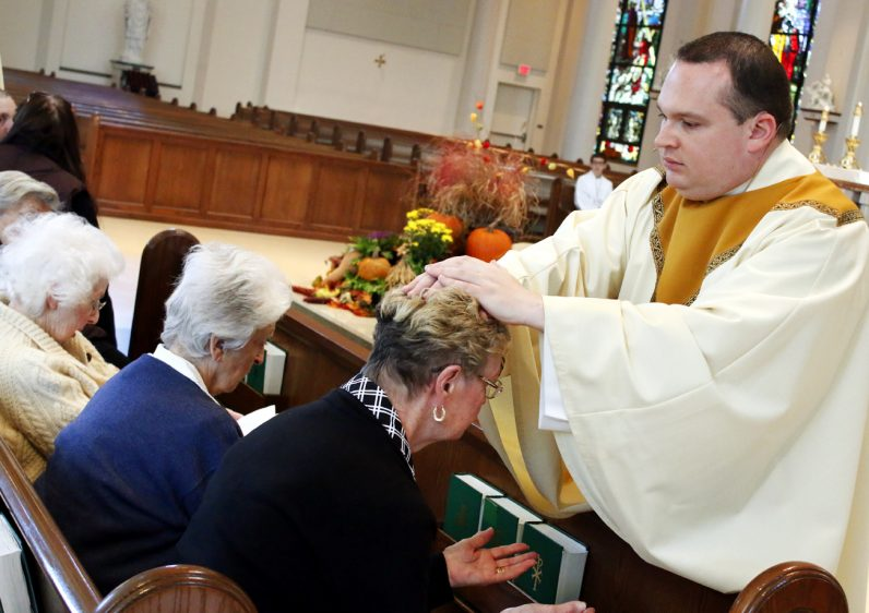 Father Anthony Rossi prays and lays hands on those attending Mass for anointing of the sick Nov. 12 at St. Joseph Church in Downingtown.