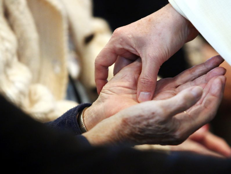 The hands and head are anointed during the rite.