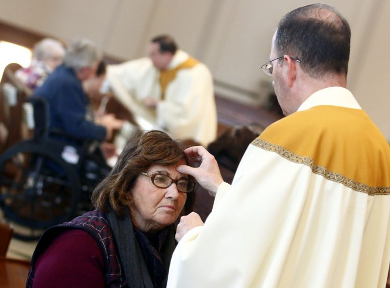 Msgr. Joseph McLoone anoints the forehead of Marianne Finnegan.