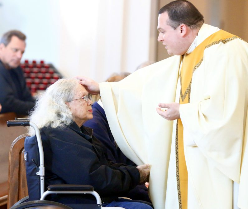 Father Anthony Rossi anoints the head of Sonia Pesquera with holy oil.