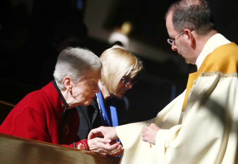 Nancy Theisen has her hands anointed by Msgr. Joseph McLoone.