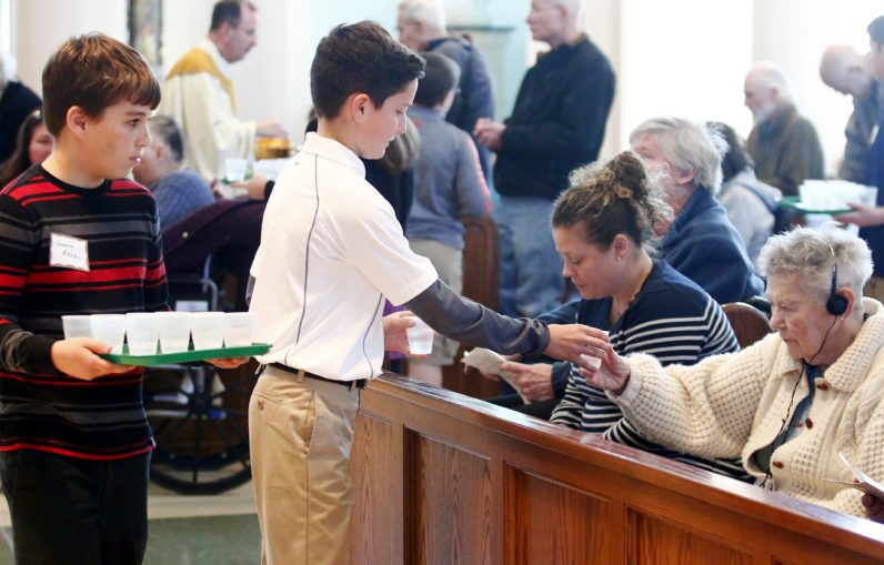 Students from the sixth grade confirmation class hand out water to those in need after they receive Communion.