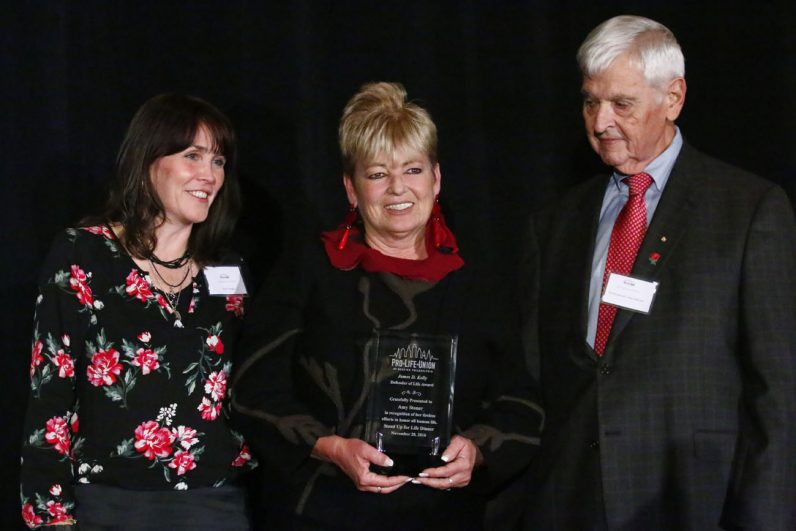 Amy Stoner, center, accepts the Pro-Life Union's Defender of Life Award for her work serving homeless people through archdiocesan Catholic Social Services. Also pictured are Edel Finnegan and Bill Wohlgemuth, executive director and chair of the Pro-Life Union, respectively.