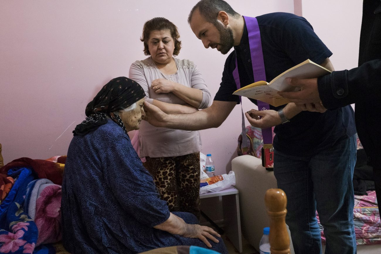 Chaldean Father Remzi Diril, also known as Father Adday, anoints Marta Kiryakos, a woman from Bartella, Iraq, who suffers from cancer, in this Nov. 10 photo. (CNS photo/Oscar Durand) See TURKEY-TRAVELING-PRIEST Nov. 28, 2016.