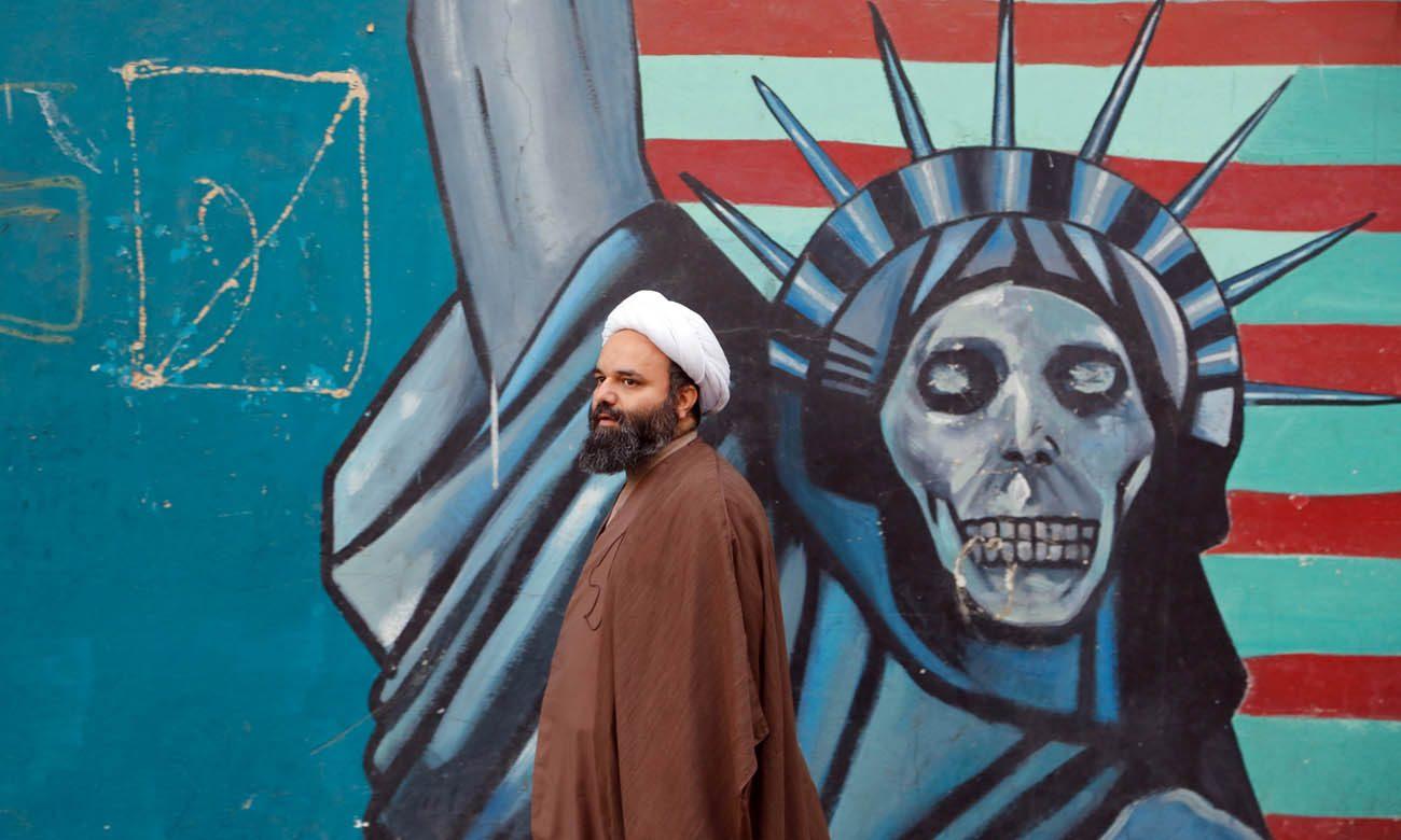 An Iranian cleric walks next to an anti-U.S. mural in Tehran Nov. 3. (CNS photo/Abedin Taherkenareh, EPA)