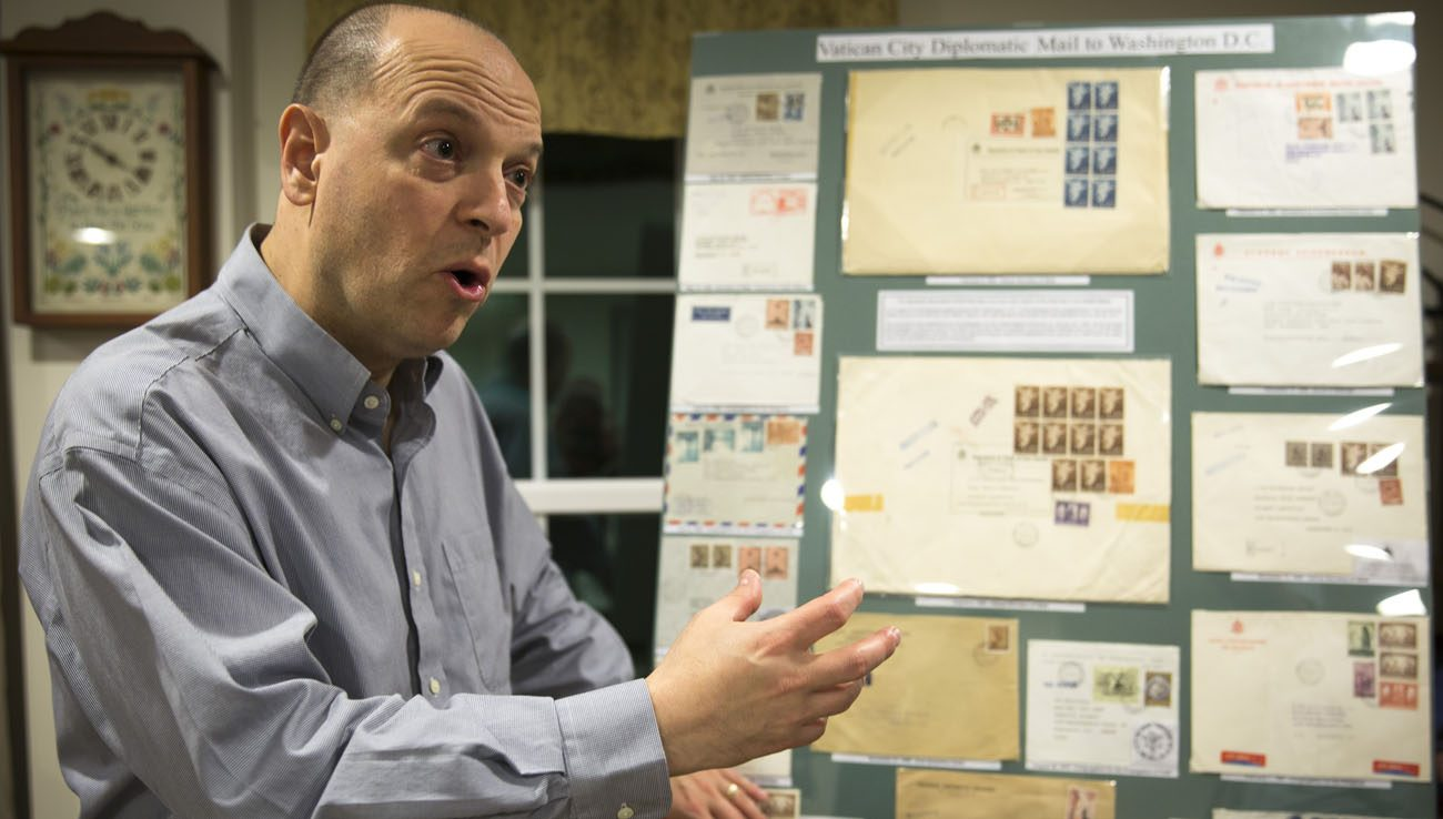 Greg Pirozzi, president of the Vatican Philatelic Society, points out a board displaying some of his Vatican stamps, notes, covers and reference material at his Hanover, Md., home Nov. 1. (CNS photo/Chaz Muth)