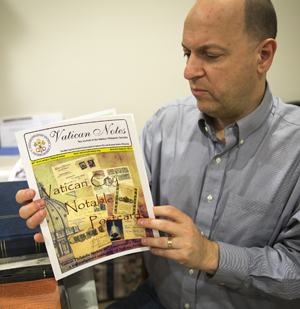 Greg Pirozzi, president of the Vatican Philatelic Society, pages through an issue of the organization's quarterly journal pertaining to some of his Vatican stamps at his Hanover, Md., home Nov. 1. (CNS photo/Chaz Muth)