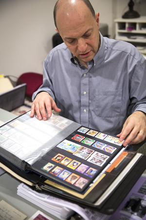 Greg Pirozzi, president of the Vatican Philatelic Society, sorts through some of his Vatican stamps, notes and reference material at his Hanover, Md., home Nov. 1. (CNS photo/Chaz Muth)