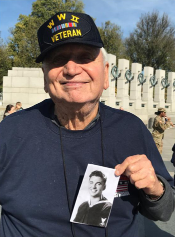 World War II veteran Burton Belenke is seen in Washington Oct. 29 holding a picture of himself when he enlisted. Behind him is the National World War II Memorial. (CNS photo/courtesy The Florida Catholic)