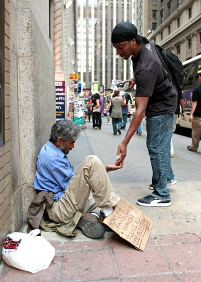 "A pedestrian gives money to a homeless man sitting outside St. Francis of Assisi Church in New York City in 2009. Poverty is ""more than an issue to be discussed or a problem to be solved,"" the Catholic bishops of Washington state said in a joint pastoral letter Nov. 17. (CNS photo/Gregory A. Shemitz)"