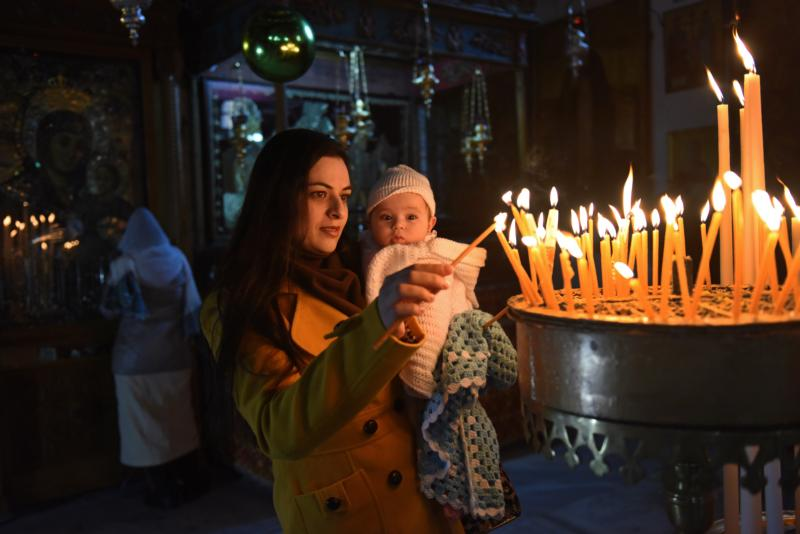 Palestinian Manan Abu Abuayash holds her baby Maram, 6 months, while lighting candles Dec. 20, 2015, in the Church of the Nativity where tradition believes Christ was born in Bethlehem, West Bank. Advent is a time of anticipation. (CNS photo/Debbie Hill)