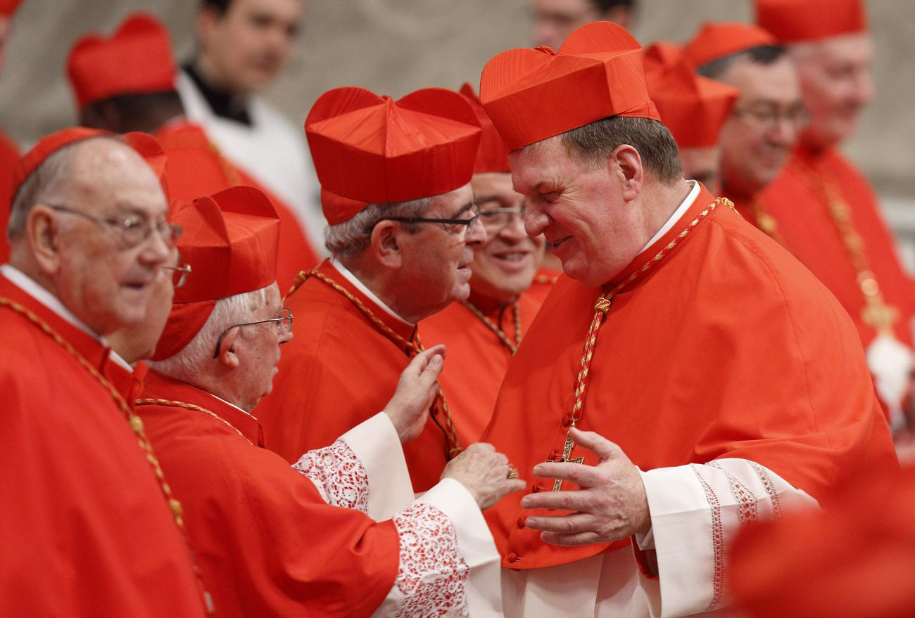 New Cardinal Joseph W. Tobin of Indianapolis, right, greets Spanish Cardinal Antonio Canizares Llovera, along with Cardinal Justin Rigali at center, during a consistory in St. Peter's Basilica at the Vatican Nov. 19. Pope Francis created 17 new cardinals at the consistory. (CNS photo/Paul Haring)