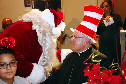 Archbishop Charles Chaput enjoys the Dr. Seuss theme of the party and its spirit, thanks to a visit with Santa Claus, a.k.a. Douglas Dunn.