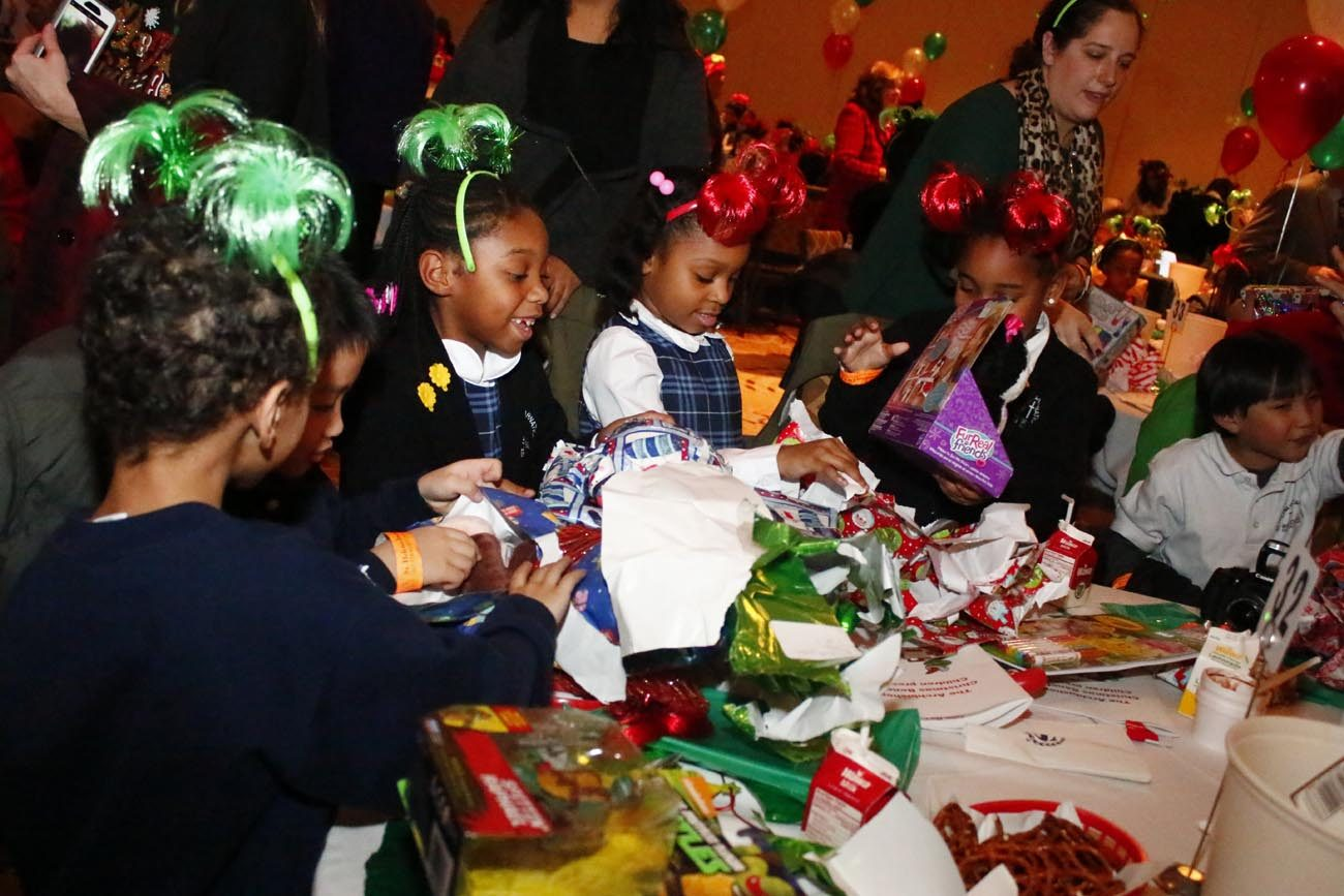 After songs, skits and lunch, children tear open presents at the annual Archbishop's Christmas Benefit for Children Dec. 19 at the Sheraton Philadelphia Center City Hotel. (Photo by Sarah Webb)