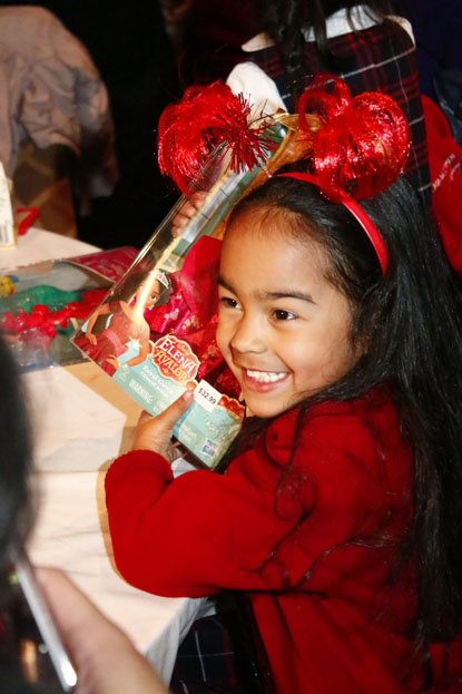 A little girl at the Archbishop's Christmas Benefit for Children is excited by her Christmas present at the party. (Sarah Webb)