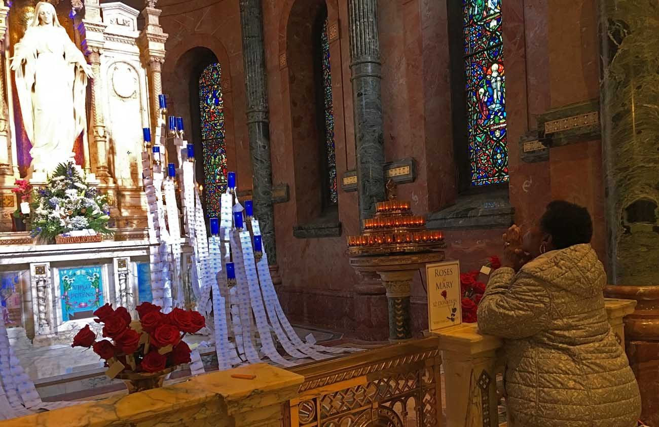 Mary Kwedu of St. Ignatius Parish in West Philadelphia joins her prayers with those of many others this Advent at the shrine to Mary at Germantown's Miraculous Medal Shrine.