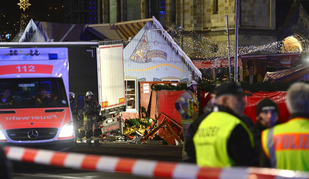 Rescue workers inspect the scene where a truck crashed into a Christmas market in Berlin Dec. 19. The terrorist attack killed at least a dozen people and injured nearly 50 as it smashed through tables and wooden stands. (CNS photo/Maurizio Gambarini, Reuters)