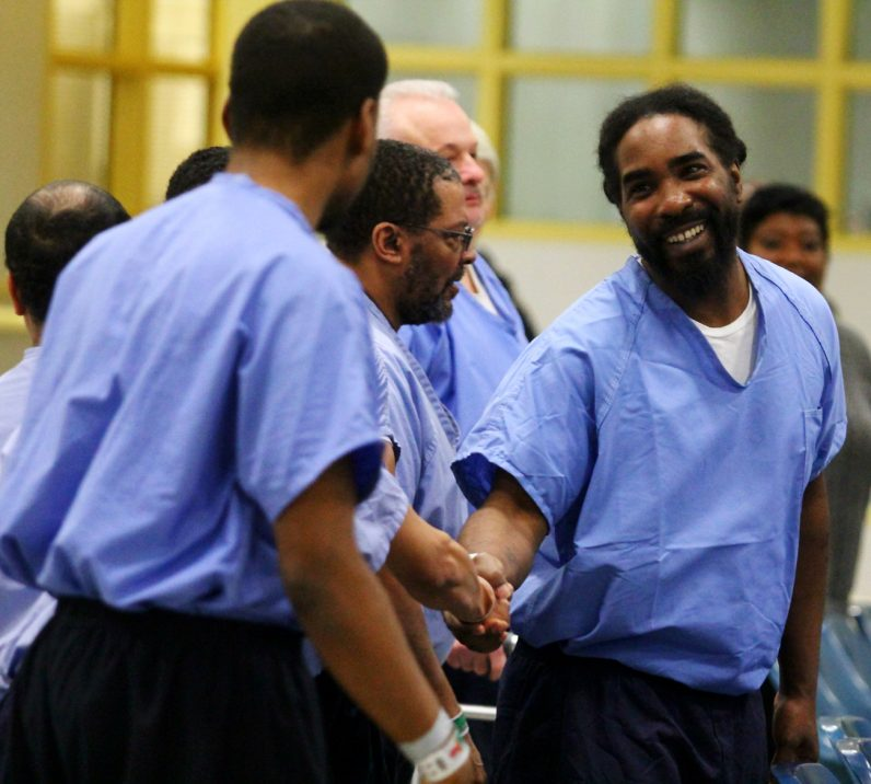 Inmates offer one another a sign of peace during Mass.