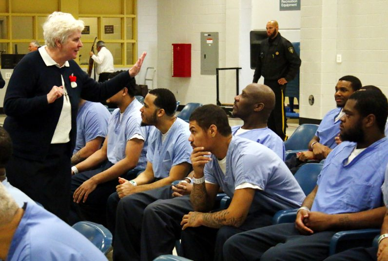 Sister Rose Patrice, who ministers to the Hispanic community and works with the prison's ministry team, speaks to prisoners attending the Mass celebrated by Archbishop Chaput.
