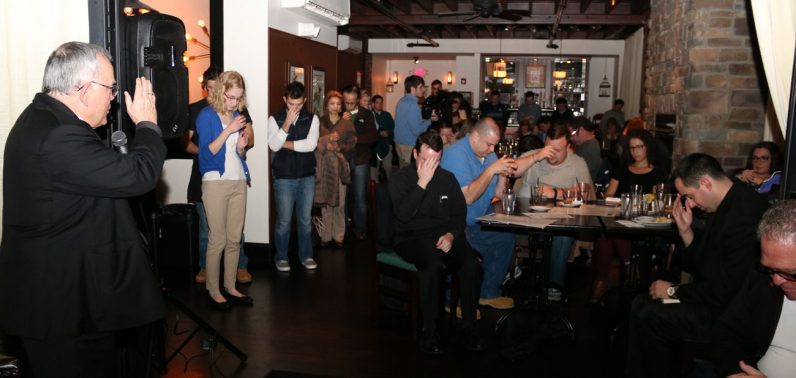 Archbishop Chaput blesses participants of the Theology on Tap session Nov. 29 at the Stove and Tap in Lansdale.