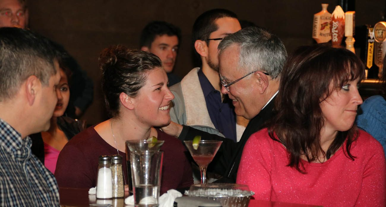 """Archbishop Charles Chaput (right) talks with Catholic young adults at the Stove and Tap in Lansdale in this Nov. 29, 2016, file photo . Tammy Becht, who will oversee St. Meinrad's program to help parishes reach out to young adults,  said the key to renewing the Catholic Church's ministry to and with young adults is to go out to where they are instead of """"waiting for them to come where we are.""""(Photo by Bob Kelly)"""