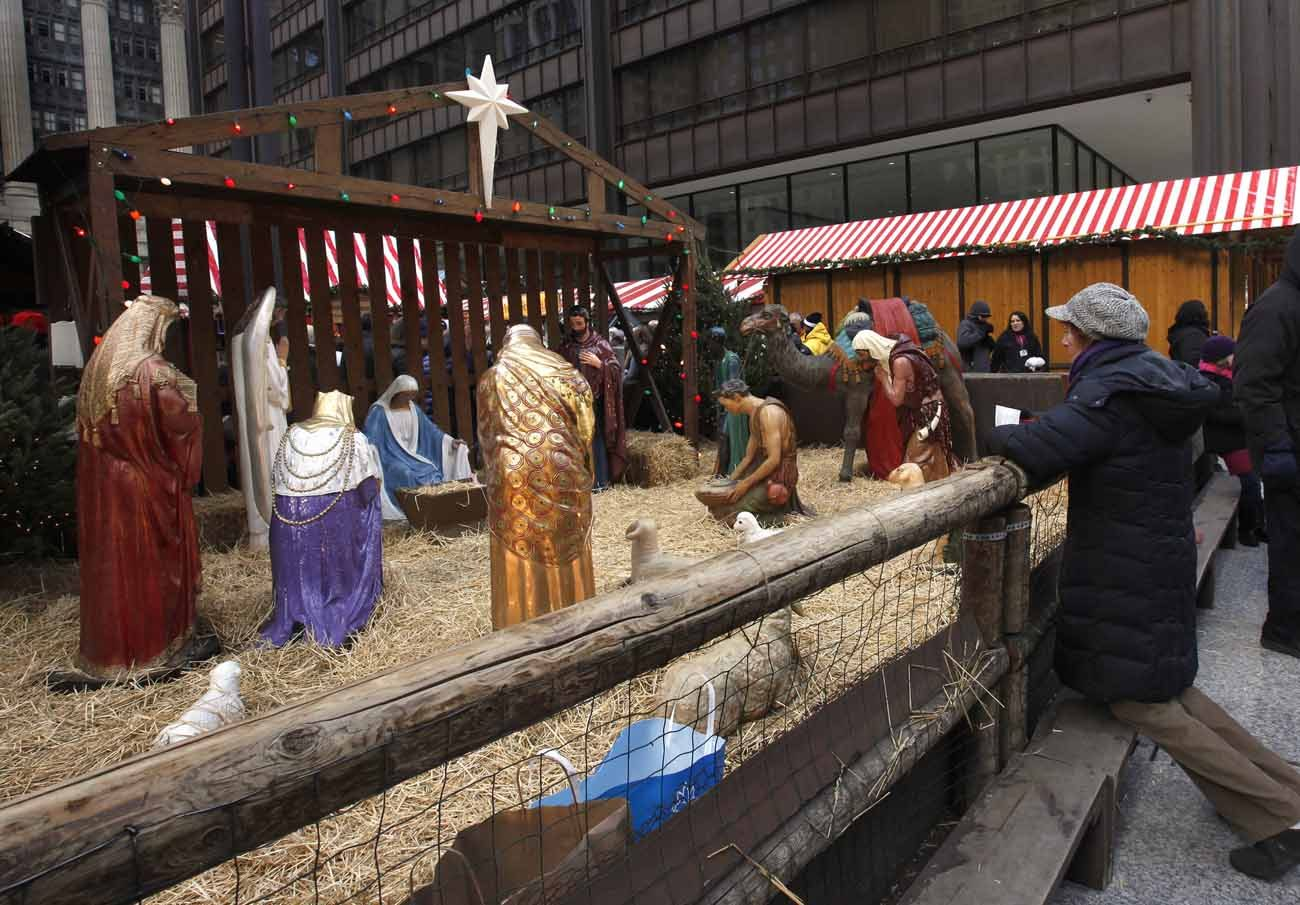 A woman prays in front of a creche in 2012 in Chicago's Daley Plaza. In his message for Christmas, Cardinal Daniel N. DiNardo of Galveston-Houston, president of the U.S. Conference of Catholic Bishops, encouraged Catholics to visit the manger this Christmas and reflect on how to give of themselves in the New Year. (CNS/Karen Callaway, Catholic New World)