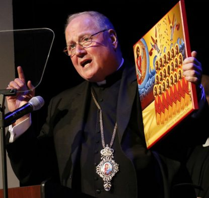 New York Cardinal Timothy M. Dolan holds an icon of the 21 Coptic Martyrs of Libya as he speaks during an interfaith forum on the crisis for Christians in the Middle East at the Sheen Center in New York City Dec. 5. (CNS photo/Gregory A. Shemitz)