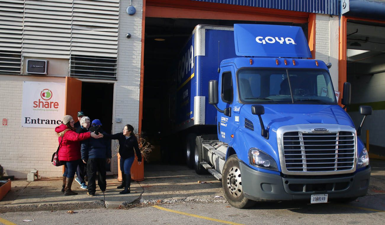 A Goya Foods truck unloads a 5,000-pound donation, for which Nutritional Development Services officials show their gratitude. (Photo by Sarah Webb)