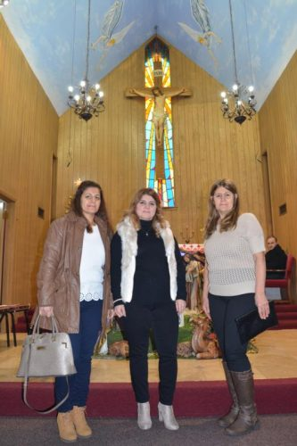 Chicago resident Fairuz Rassam, center, poses with her siblings Firaz Rassam and Victoria Rassam, after Mass Dec. 4 at St. Ephrem Chaldean Catholic Church in Chicago. (CNS photo/Simone Orendain)