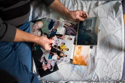 Sami Dankha, 51, looks at old family photographs Nov. 21; he brought them from Iraq to Istanbul, where he is now a refugee. He lives In Istanbul with his wife and five children; his brothers live in New Zealand, Australia and the Netherlands. (CNS photo/Oscar Durand)