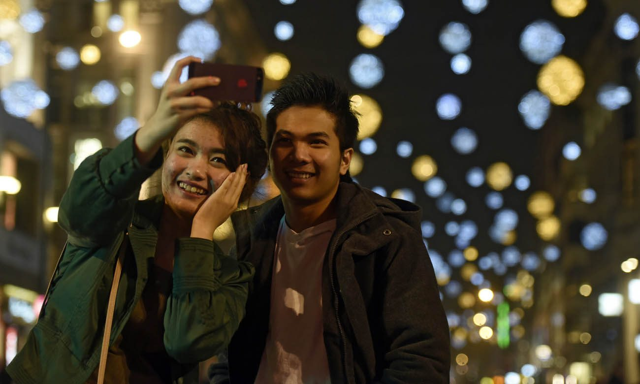 A couple takes a selfie in 2015 in front of the Oxford Street Christmas Lights moments after they switched on in London. People who work with married couples have urged them to make time for each other, especially during the often-stressful Christmas season. (CNS photo/Hannah McKay, EPA)