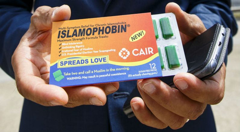 """A man near the Republican National Convention in Cleveland in July holds a pack of chewing gum called '""""Islamophobin."""" The packaging attempts to bring attention to the issue of anti-Muslim attitudes in the United States. (CNS photo/Justin Lane, EPA)"""