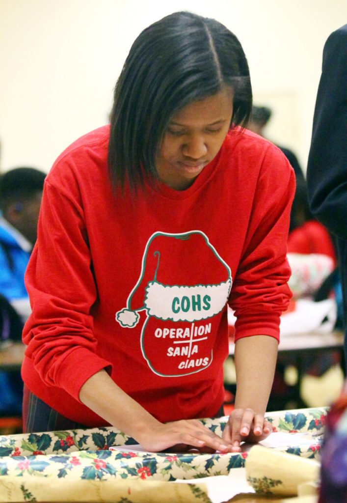 Cardinal O'Hara junior Breanna Johnson makes sure the wrapping paper lines up just right for the toy she bought for a child in need.